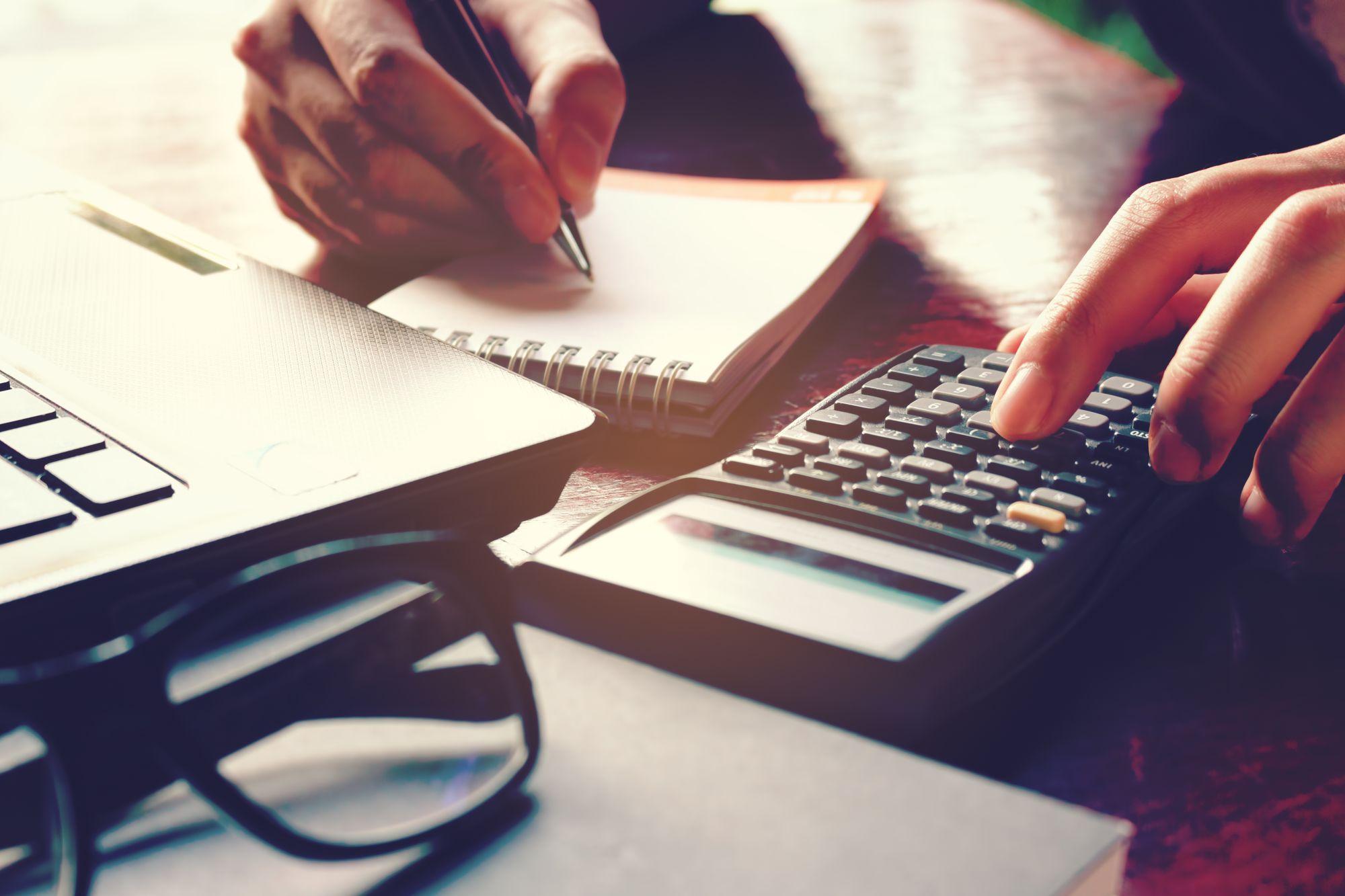 mężczyzna pracujący przy komputerze z kalkulatorem